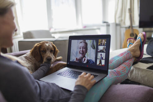 Woman with laptop video chatting with friends on sofa with dog - CAIF28843