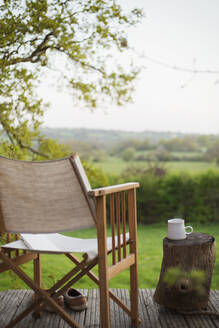 Book and chair on balcony overlooking rural field - CAIF28972