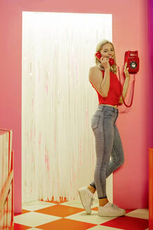 Smiling young woman talking over telephone while standing indoors - BFRF02277