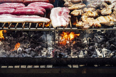 Close-up of meat and coals on barbecue grill in yard - JCMF01058