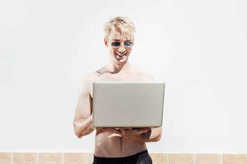 Wet shirtless young man wearing sunglasses using laptop while standing against wall - JCMF01073