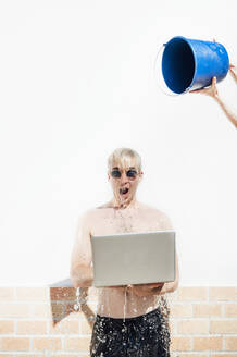 Mid adult woman pouring water with bucket on shirtless young man using laptop against wall - JCMF01076