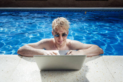 Shirtless handsome man wearing sunglasses using laptop at poolside - JCMF01079