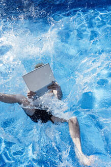Young man with laptop falling in swimming pool during sunny day - JCMF01082