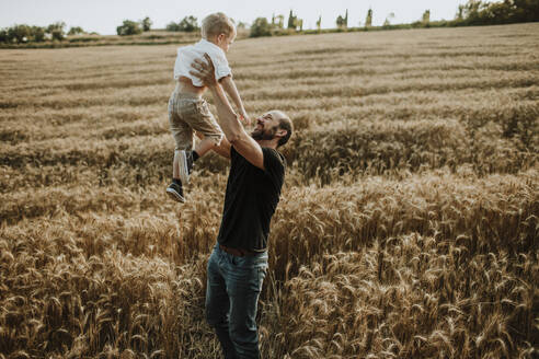 Father spending leisure time with son in wheat farm - GMLF00350