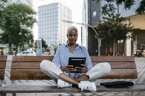 Businesswoman with digital tablet sitting on bench in city - JRFF04622