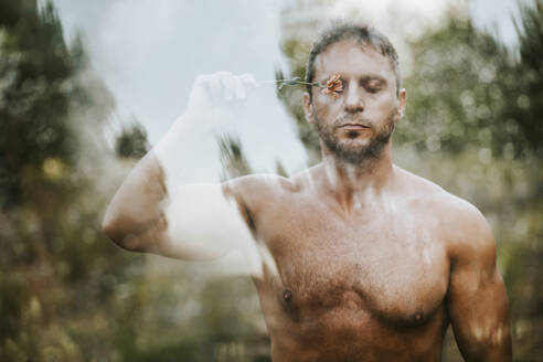 Shirtless handsome man with eyes closed holding flower on eye in forest seen through glass - MIMFF00094