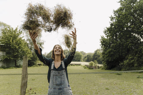 Happy young woman in the countryside throwing up hay - GUSF04228