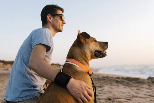 Man and dog looking away while sitting at beach - EGAF00596
