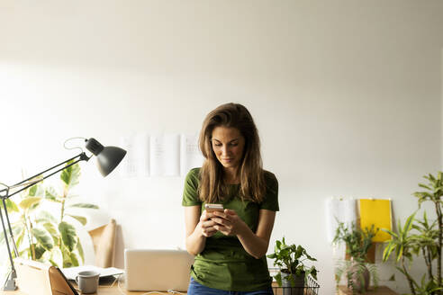 Woman using smart phone while standing at desk in home office - VABF03202