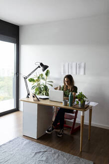 Businesswoman working over laptop on desk in home office - VABF03214