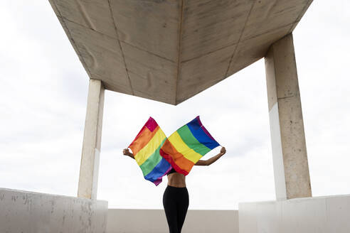 Mid adult woman waving rainbow flags while standing on built structure against sky - VABF03286
