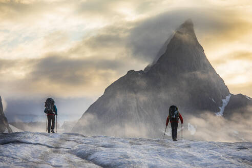 Two backpackers hiking towards Mt. Loki, Baffin Island, Canada. - CAVF87636