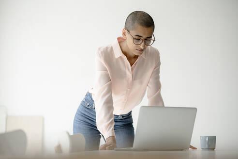 Businesswoman using laptop at desk in loft office - KNSF08268