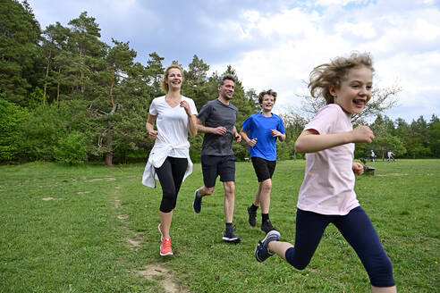 Cheerful family running on meadow against trees in forest - ECPF00993