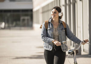 Smiling female commuter listening music while walking with bicycle on street in city - UUF20776