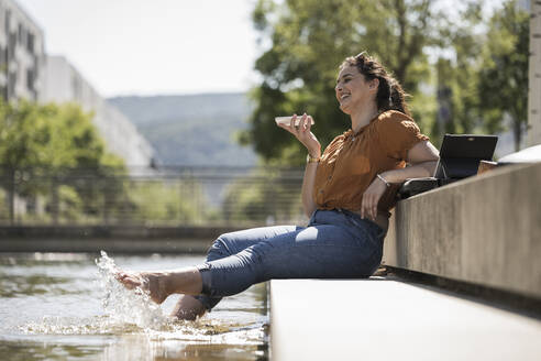 Cheerful woman with legs in pond talking over smart phone while sitting at park - UUF20794