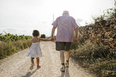 Grandfather holding granddaughter's hand while walking on dirt road against sky - JRFF04651