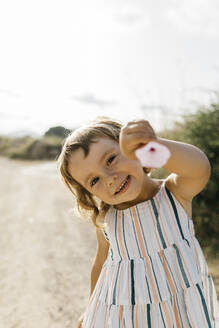 Close-up of happy girl showing flower while standing against sky during sunny day - JRFF04657