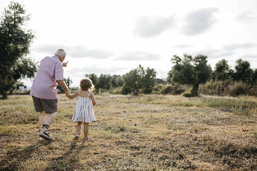 Grandfather with granddaughter walking on grassy land against sky - JRFF04660