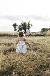 Grandfather and granddaughter walking on grassy land against sky - JRFF04666