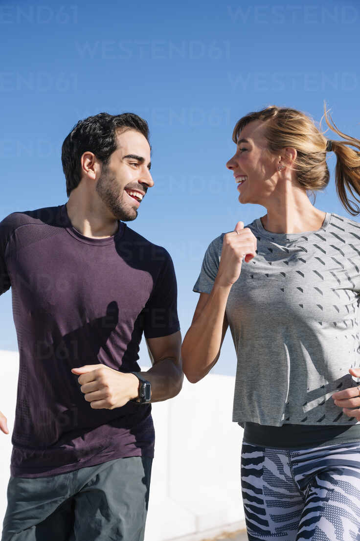 Smiling couple looking at each other while running against clear blue sky on sunny day - JCMF01096 - Jose Luis CARRASCOSA/Westend61