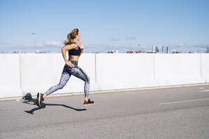 Mid adult woman running on road against blue sky in city during sunny day - JCMF01099