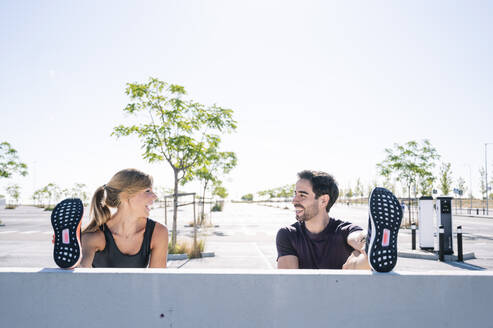 Smiling couple with feet up exercising on retaining wall against clear sky during sunny day - JCMF01102