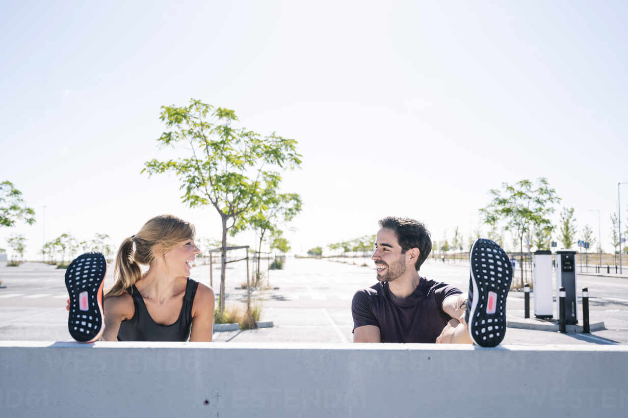 Smiling couple with feet up exercising on retaining wall against clear sky during sunny day - JCMF01102 - Jose Luis CARRASCOSA/Westend61