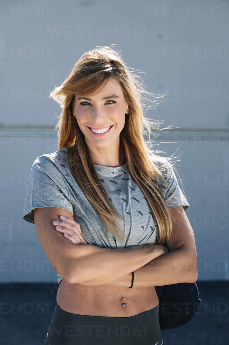 Smiling mid adult woman with arms crossed standing against wall in city - JCMF01111 - Jose Luis CARRASCOSA/Westend61