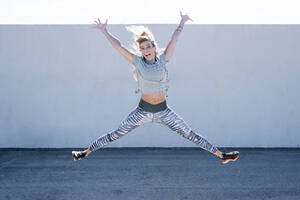 Cheerful mid adult woman with arms raised jumping on road against wall in city - JCMF01114