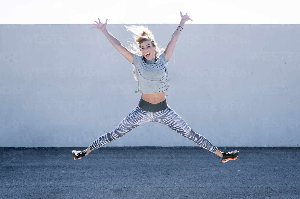 Cheerful mid adult woman with arms raised jumping on road against wall in city - JCMF01114 - Jose Luis CARRASCOSA/Westend61