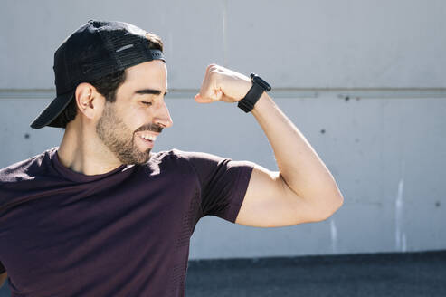 Close-up of man with eyes closed flexing muscle against wall in city - JCMF01117
