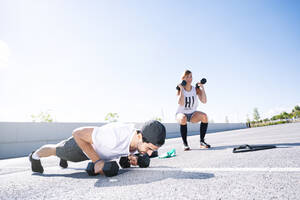 Couple with dumbbells exercising on road against clear sky during sunny day - JCMF01120