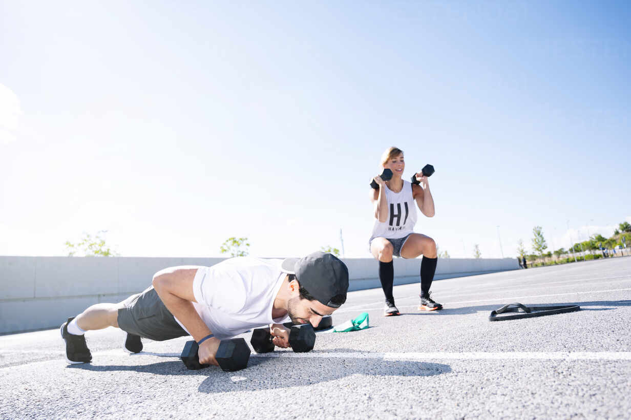 Couple with dumbbells exercising on road against clear sky during sunny day - JCMF01120 - Jose Luis CARRASCOSA/Westend61
