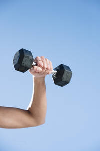 Close-up of mid adult woman lifting dumbbell against clear blue sky - JCMF01123