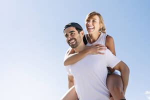 Mid adult man piggybacking cheerful woman against clear sky during sunny day - JCMF01126