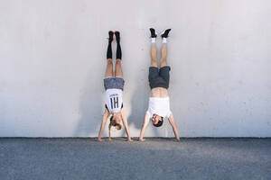Couple doing handstands on road against wall in city - JCMF01129