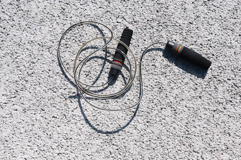 High angle view of skipping rope on road during sunny day - JCMF01135