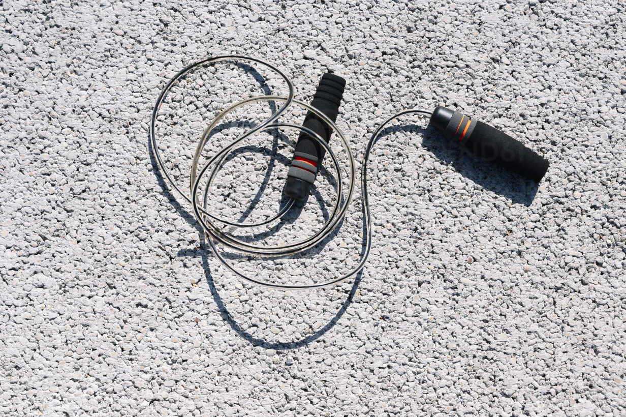 High angle view of skipping rope on road during sunny day - JCMF01135 - Jose Luis CARRASCOSA/Westend61