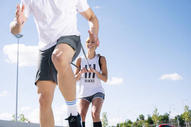 Smiling woman holding strap while exercising with boyfriend against sky during sunny day - JCMF01138