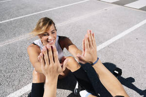 Smiling woman giving high-five to boyfriend while exercising on road in city - JCMF01141