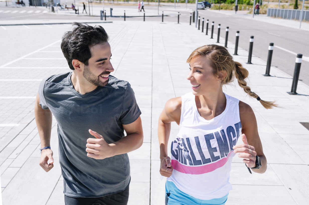 Smiling couple looking at each other while running on sidewalk in city - JCMF01144 - Jose Luis CARRASCOSA/Westend61