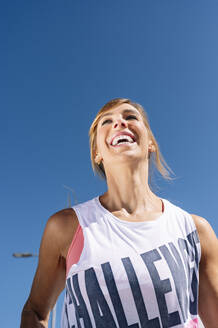 Mid adult woman laughing while running against clear blue sky during sunny day - JCMF01147