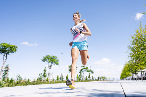 Mid adult woman jogging on street against blue sky - JCMF01150