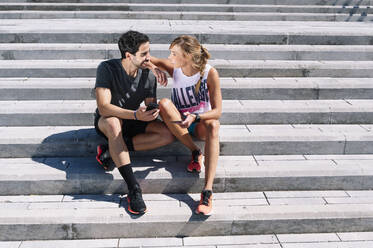 Smiling couple looking at each other while sitting on steps in city during sunny day - JCMF01153