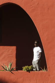 Young man wearing sunglasses standing by red wall during sunny day - LJF01686
