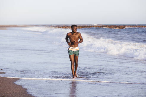 Shirtless African young man running at shore against clear sky - LJF01707