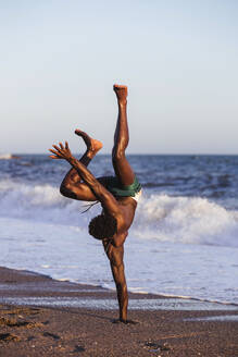 Shirtless young man doing handstand at beach against clear sky - LJF01710