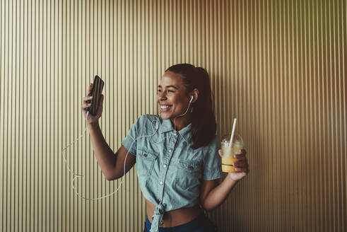 Cheerful woman holding smart phone and drink while enjoying music through headphones against wall - DSIF00065